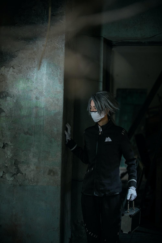 woman in black jacket standing beside gray concrete wall