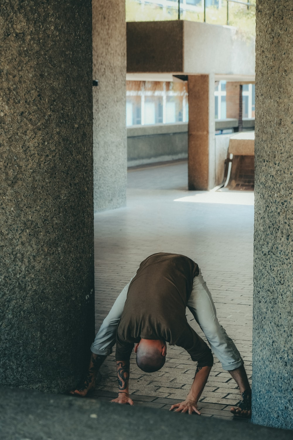 person in black leather jacket and gray pants lying on floor