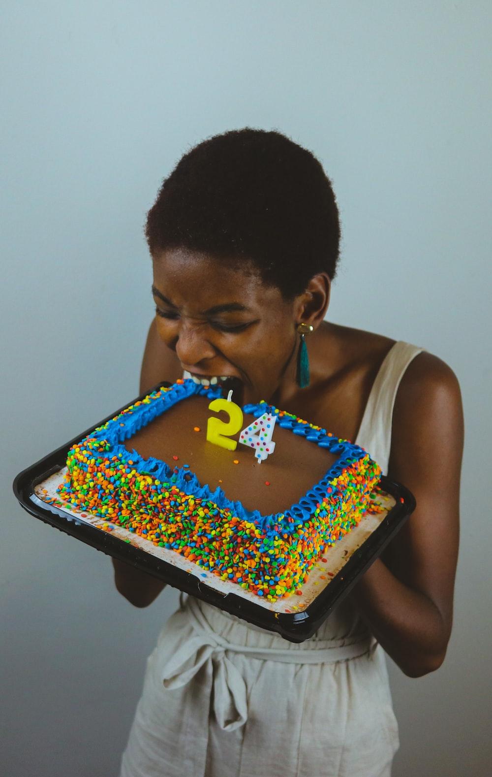 man in white tank top holding cake