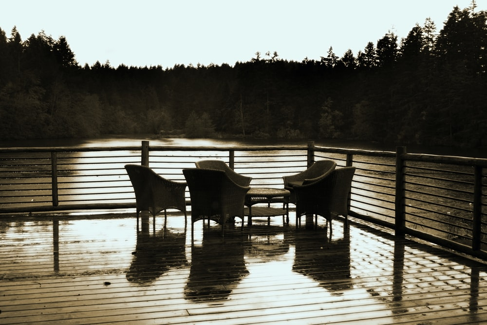 grayscale photo of two wooden chairs on wooden dock