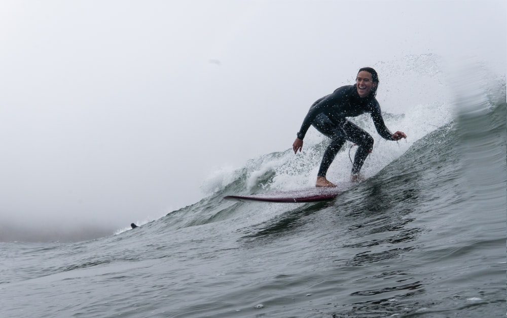 man in black wet suit riding on red surfboard on sea waves during daytime