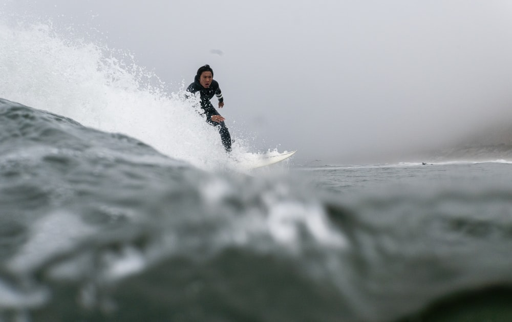 man in black and orange wet suit surfing on sea waves during daytime