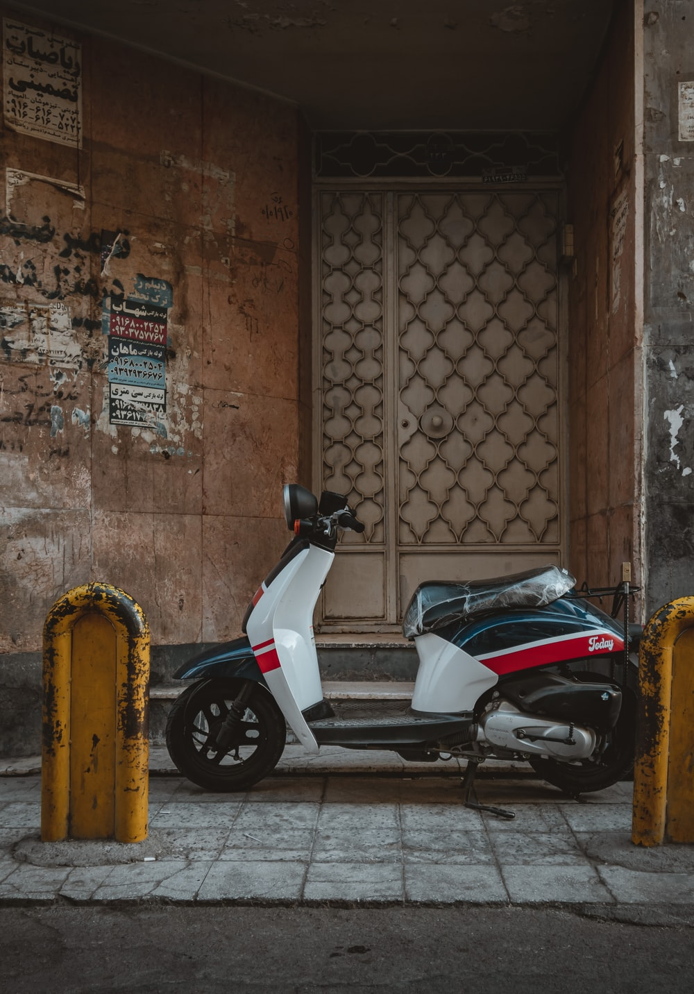 white and black motor scooter parked beside brown brick wall