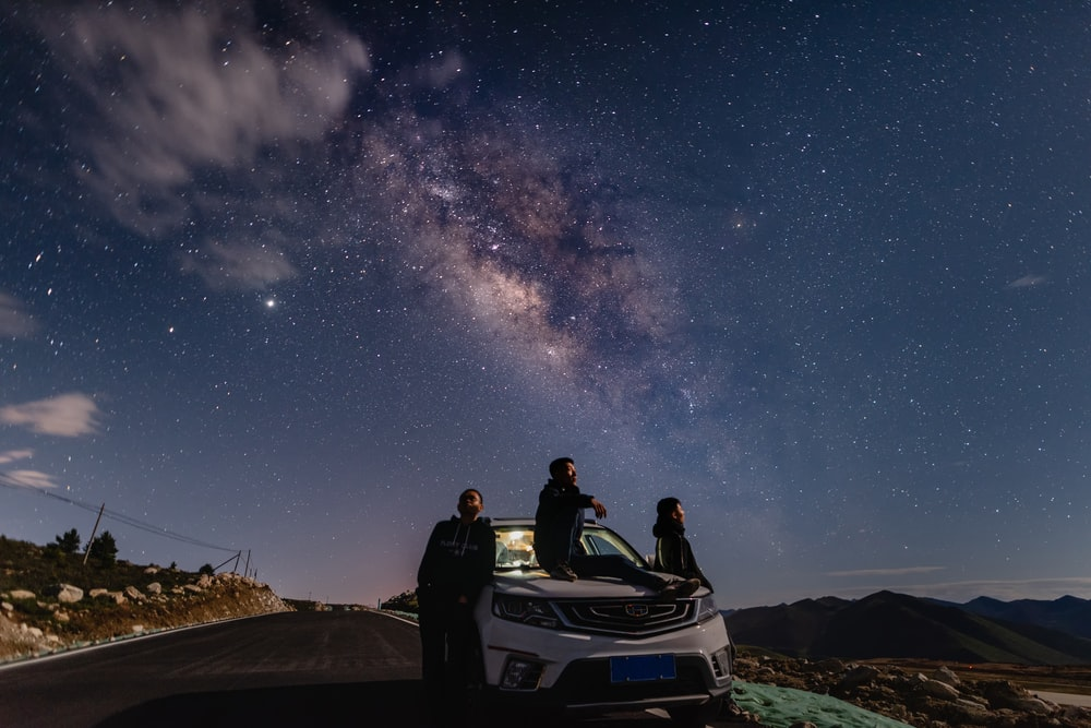 couple sitting on white and blue convertible car under starry night