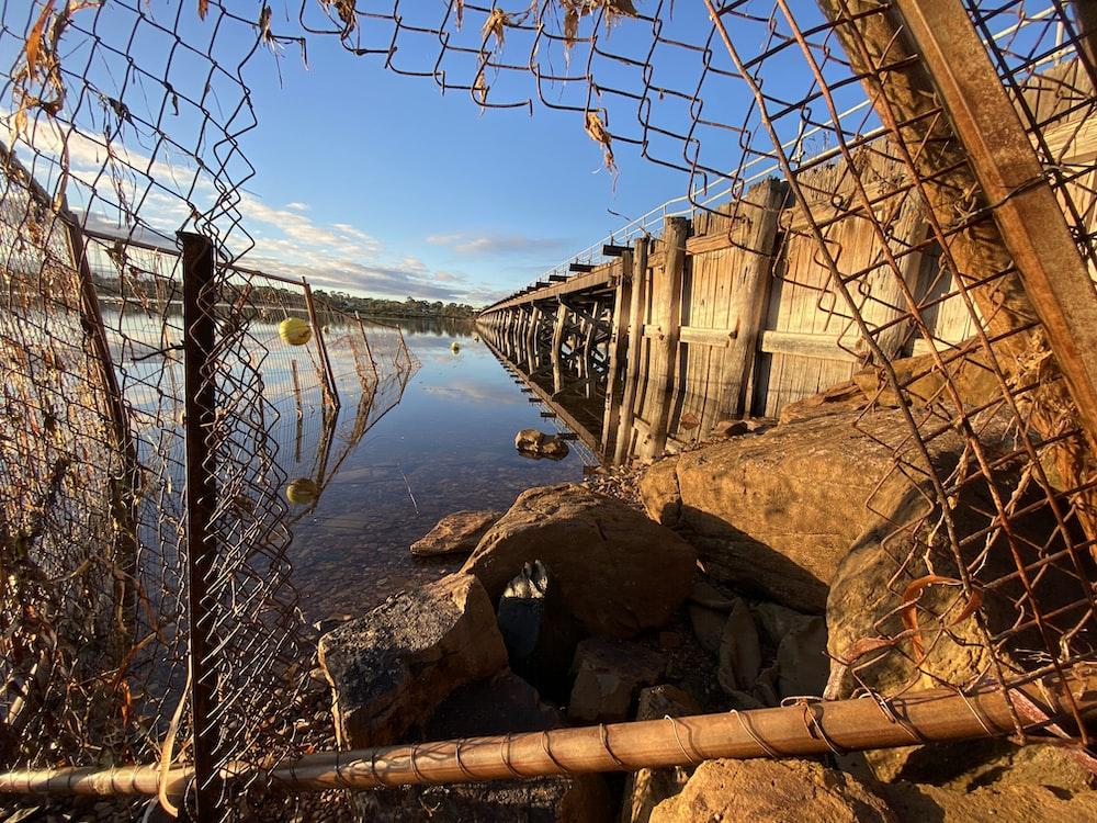 brown wooden bridge over blue sea during daytime