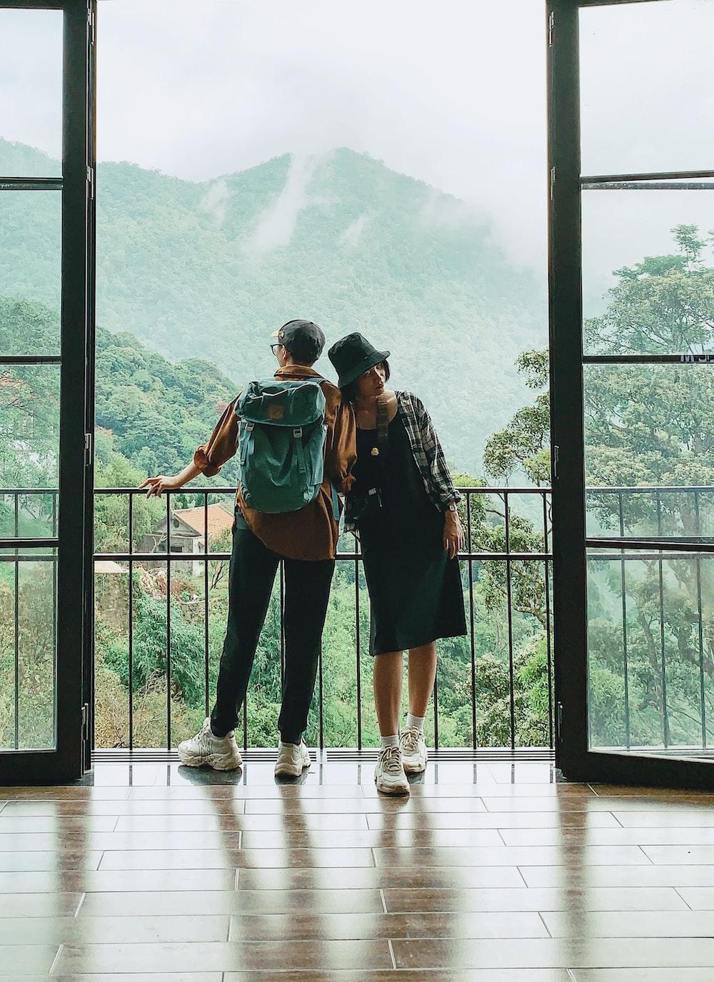 2 women standing on white wooden floor during daytime