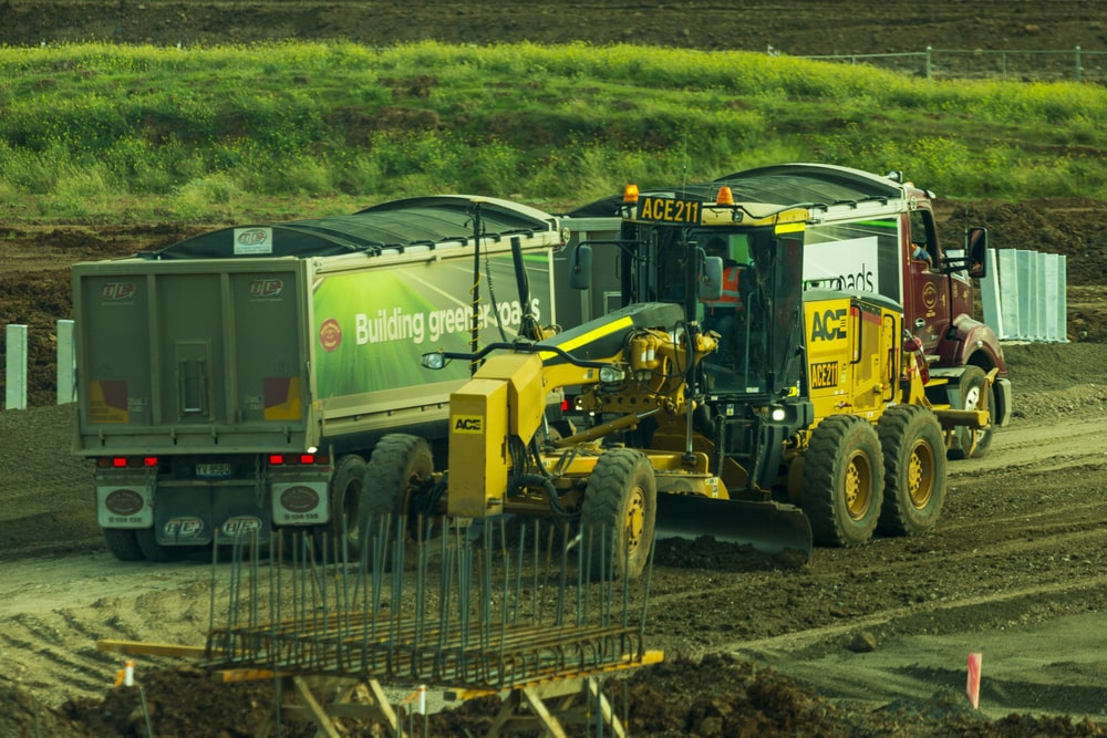 yellow and black heavy equipment on brown soil