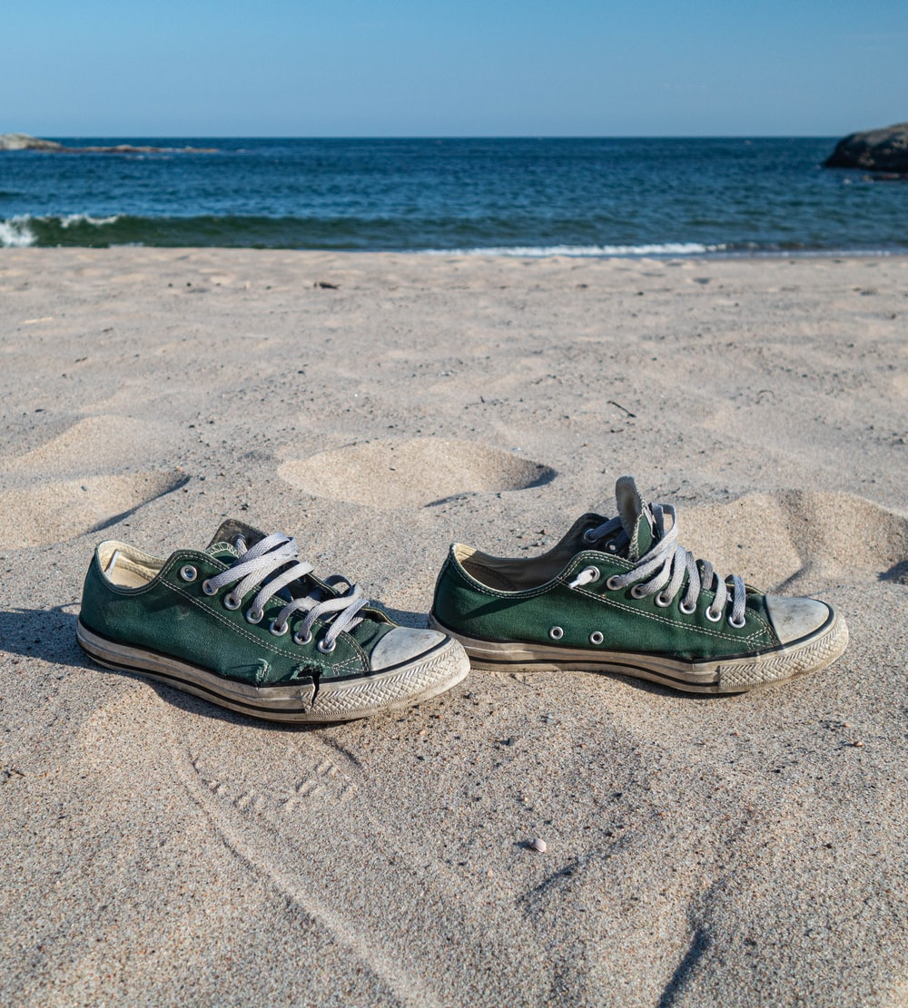 black and white nike sneakers on beach sand