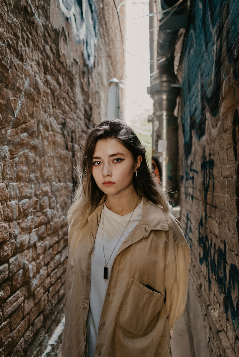 woman in brown coat standing beside brown brick wall during daytime
