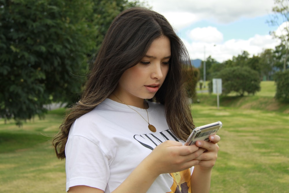 woman in white crew neck t-shirt holding silver iphone 6