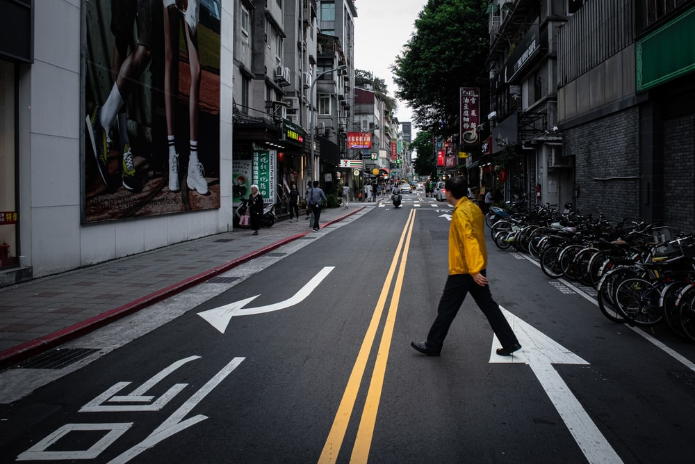 man in yellow jacket and black pants walking on pedestrian lane during daytime