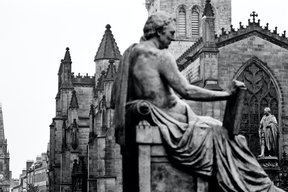 woman sitting on concrete statue