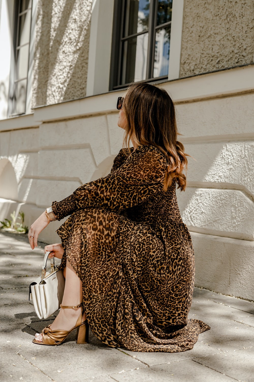 woman in brown and black leopard print dress holding white leather handbag