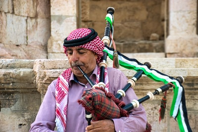 man in red and white long sleeve shirt playing flute bagpipe teams background