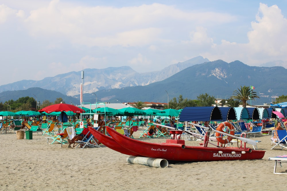 red boat on beach during daytime
