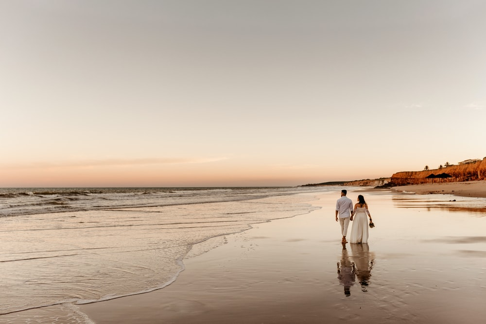 woman in white dress walking on beach during sunset