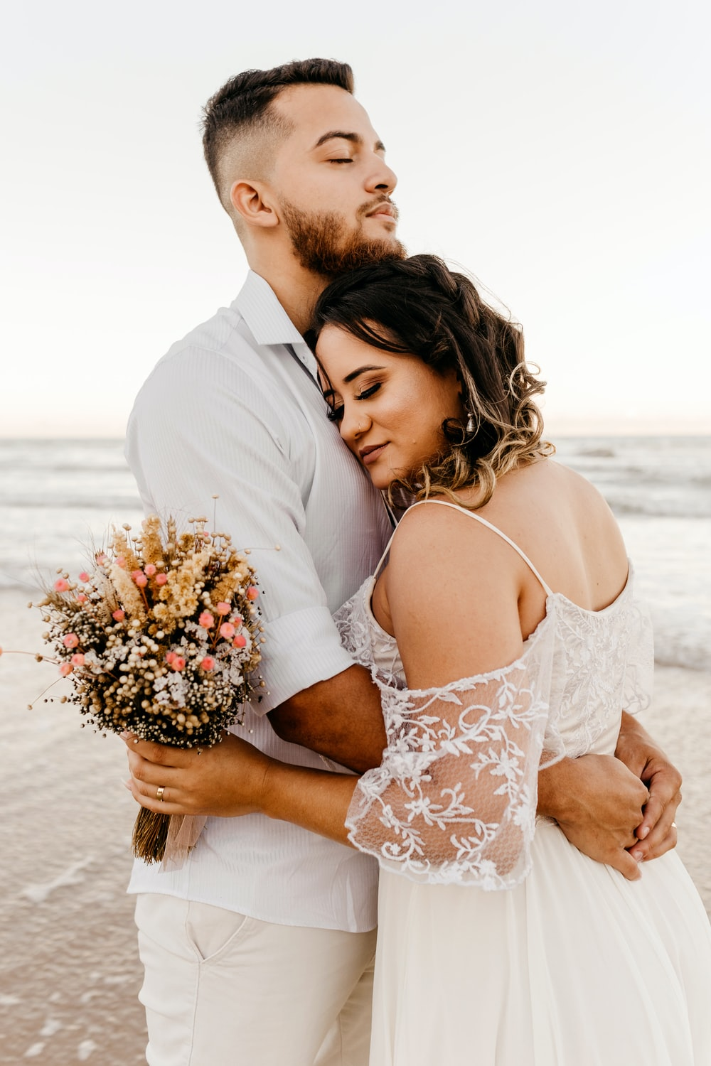 man in white suit kissing woman in white floral dress on beach during daytime