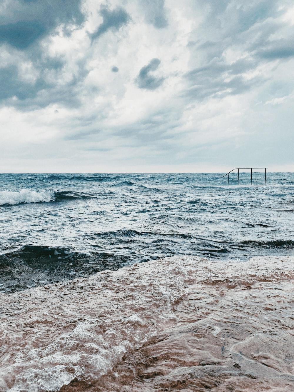 ocean waves crashing on beach shore during daytime