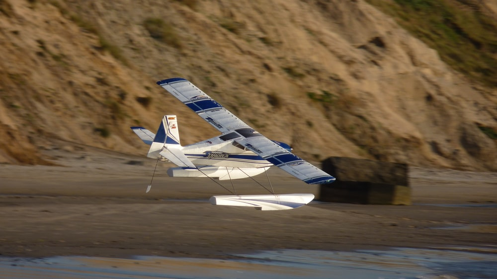 white and blue airplane on brown field during daytime