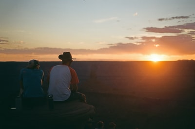 man in white t-shirt sitting on bench during sunset cowboys teams background