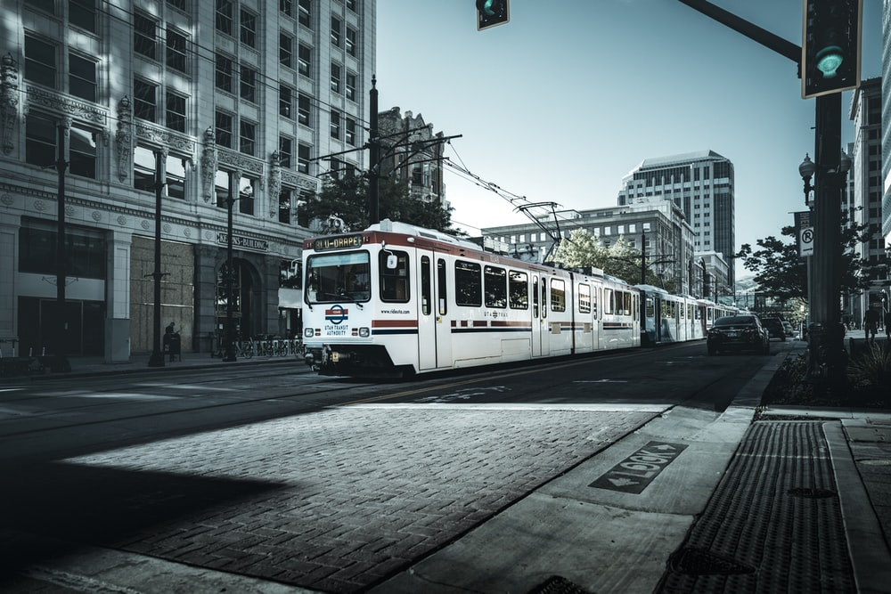 white and red tram on road during daytime