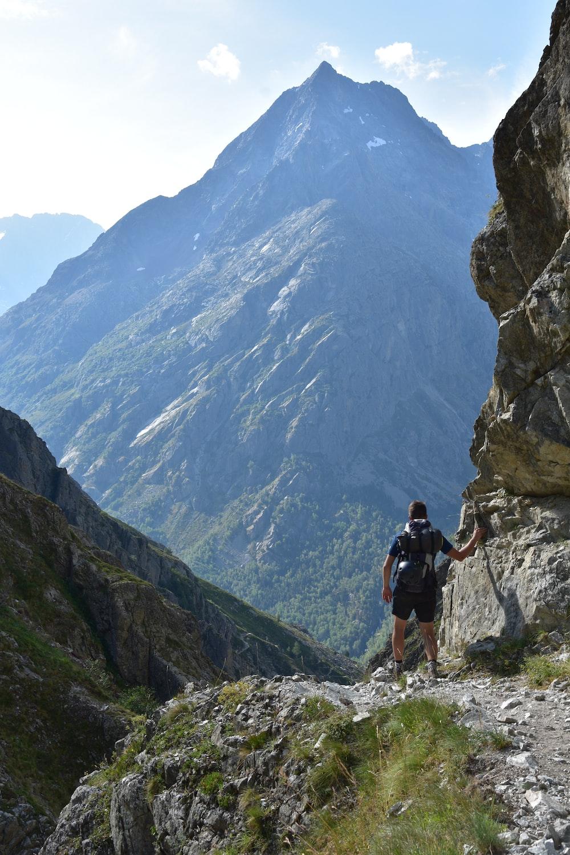 man in black shirt and black shorts walking on rocky mountain during daytime