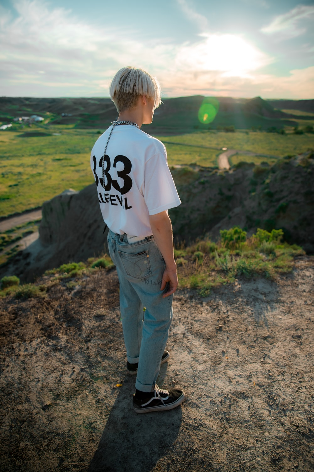 boy in white t-shirt and blue denim jeans standing on dirt ground during daytime
