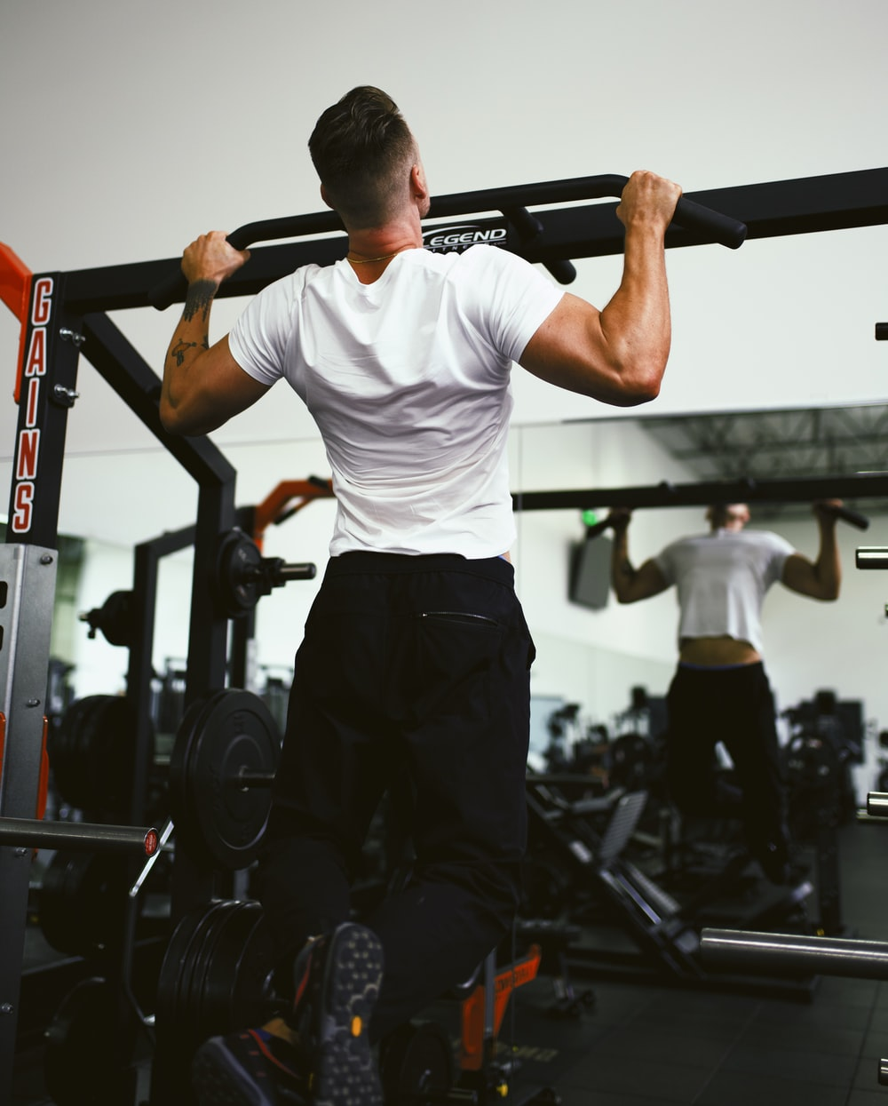man in white crew neck t-shirt and black pants holding black exercise equipment