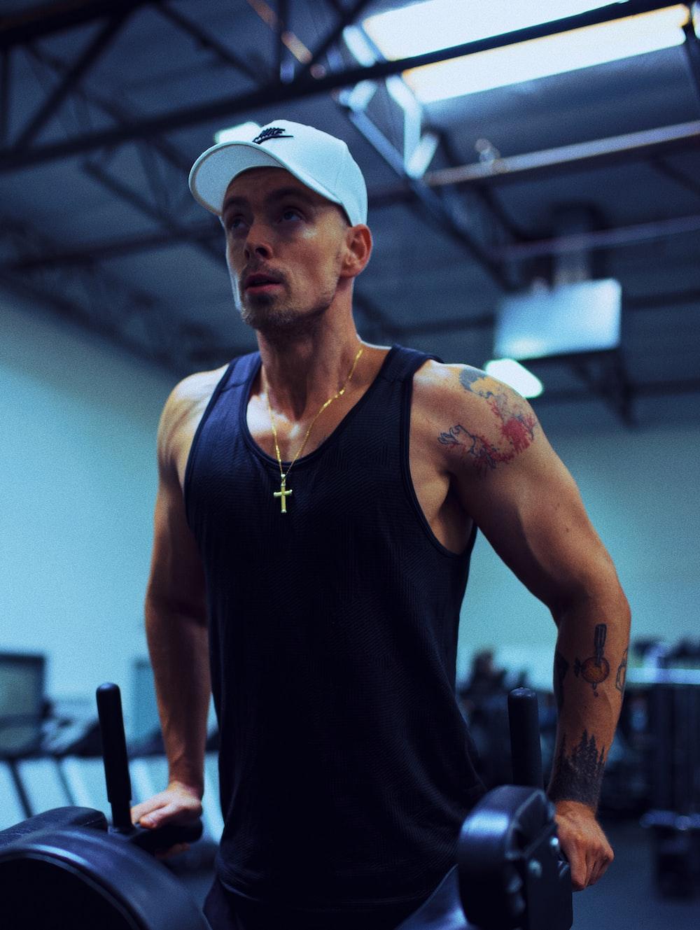 man in black tank top wearing white cap