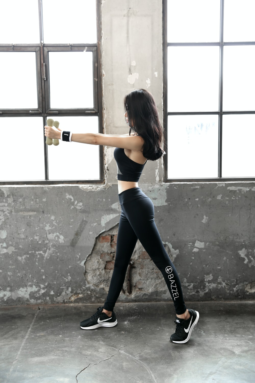 woman in black sports bra and black leggings holding bottle