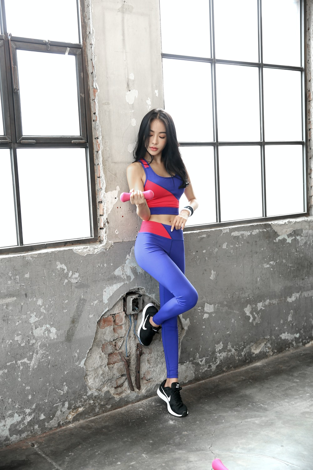 woman in blue leggings and black shoes sitting on concrete wall