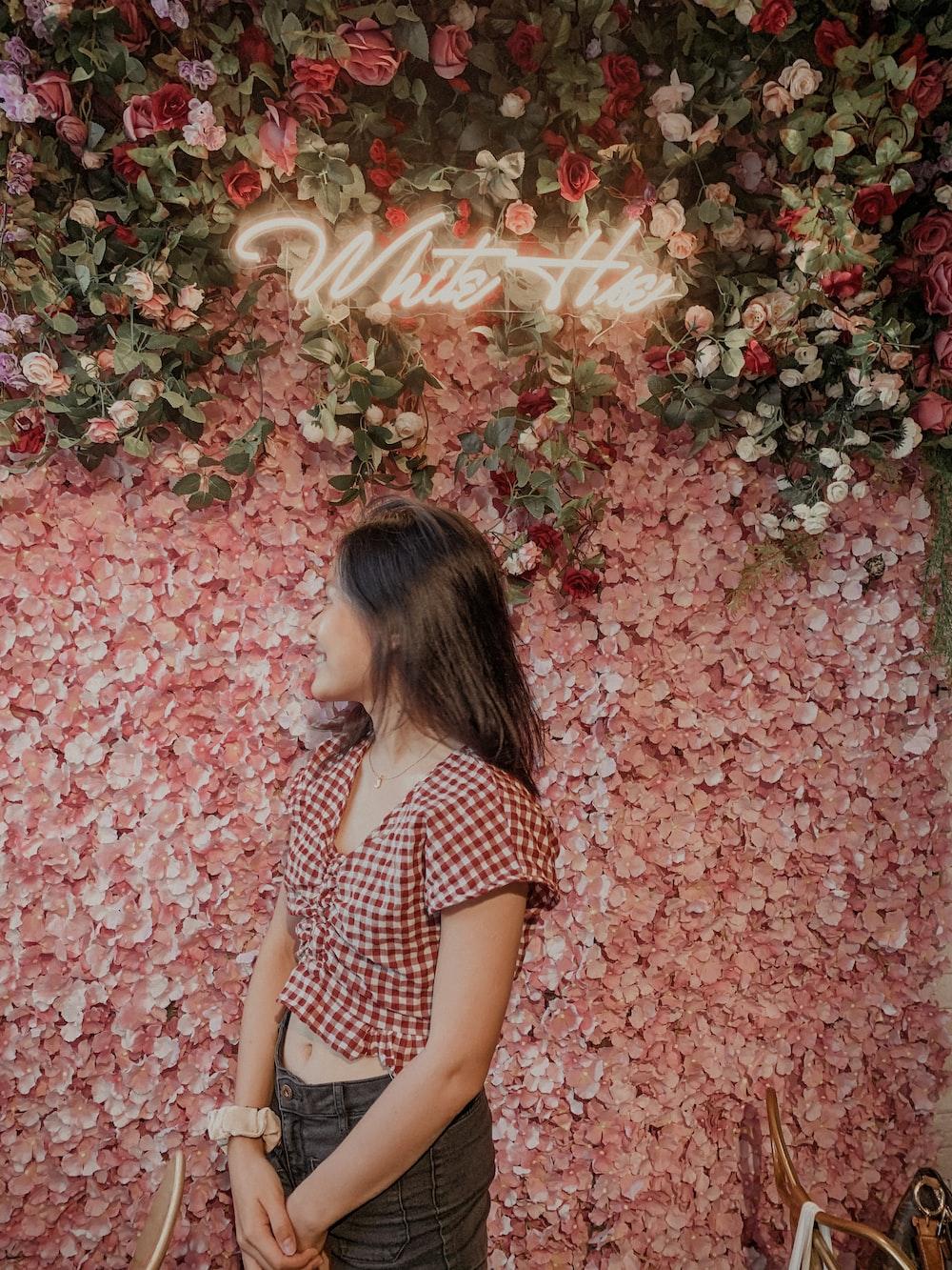 girl in black and white polka dot shirt standing on red leaves