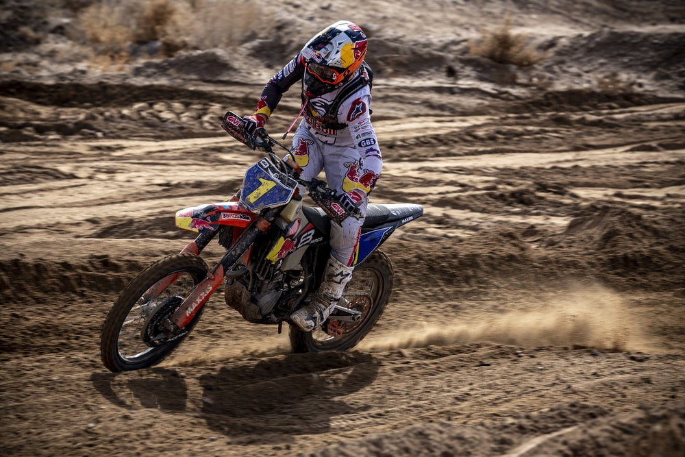 man in blue and white motorcycle suit riding motocross dirt bike on brown sand during daytime