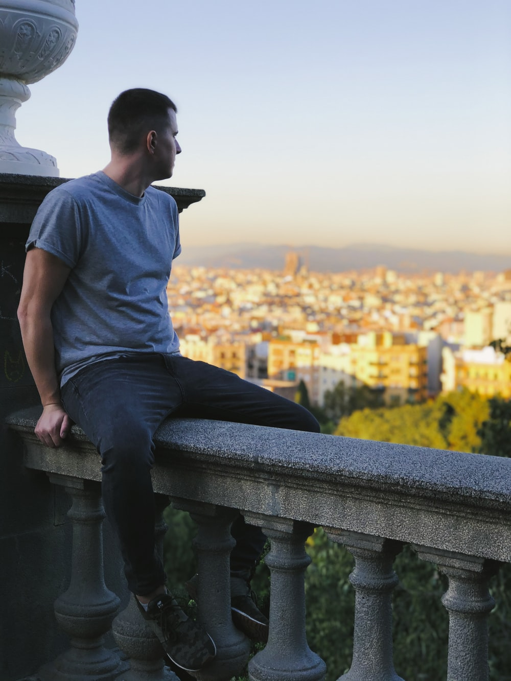 man in gray crew neck t-shirt and blue denim jeans sitting on gray concrete bench
