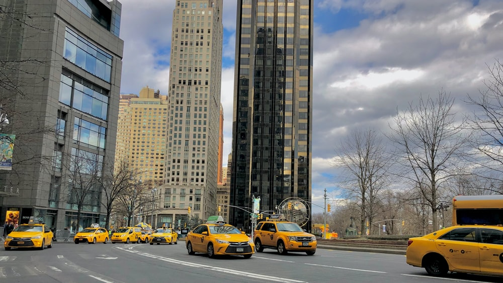 yellow car on road near high rise buildings during daytime