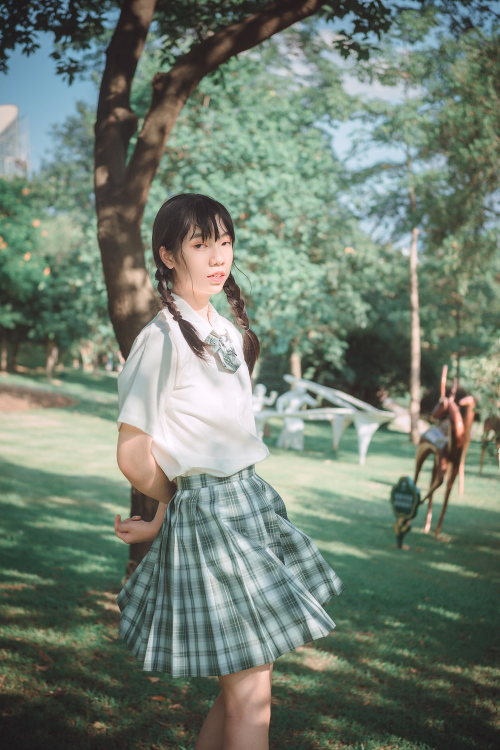 woman in white shirt and black and white plaid skirt standing on green grass field during