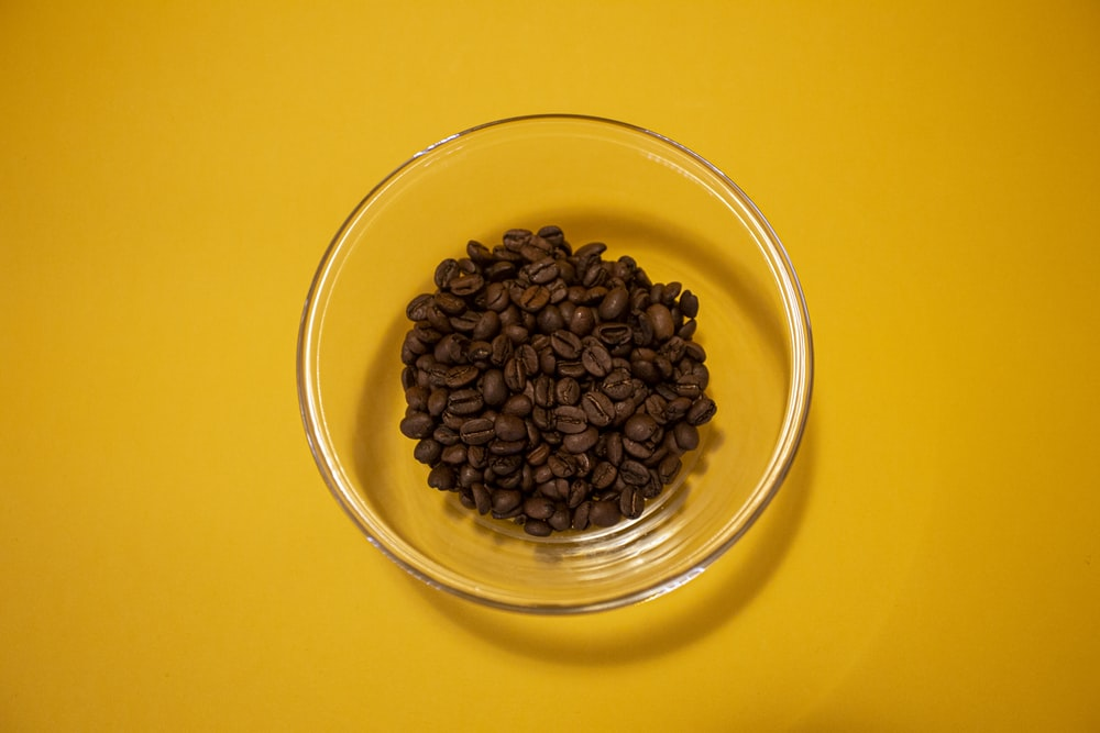 brown coffee beans in clear glass bowl