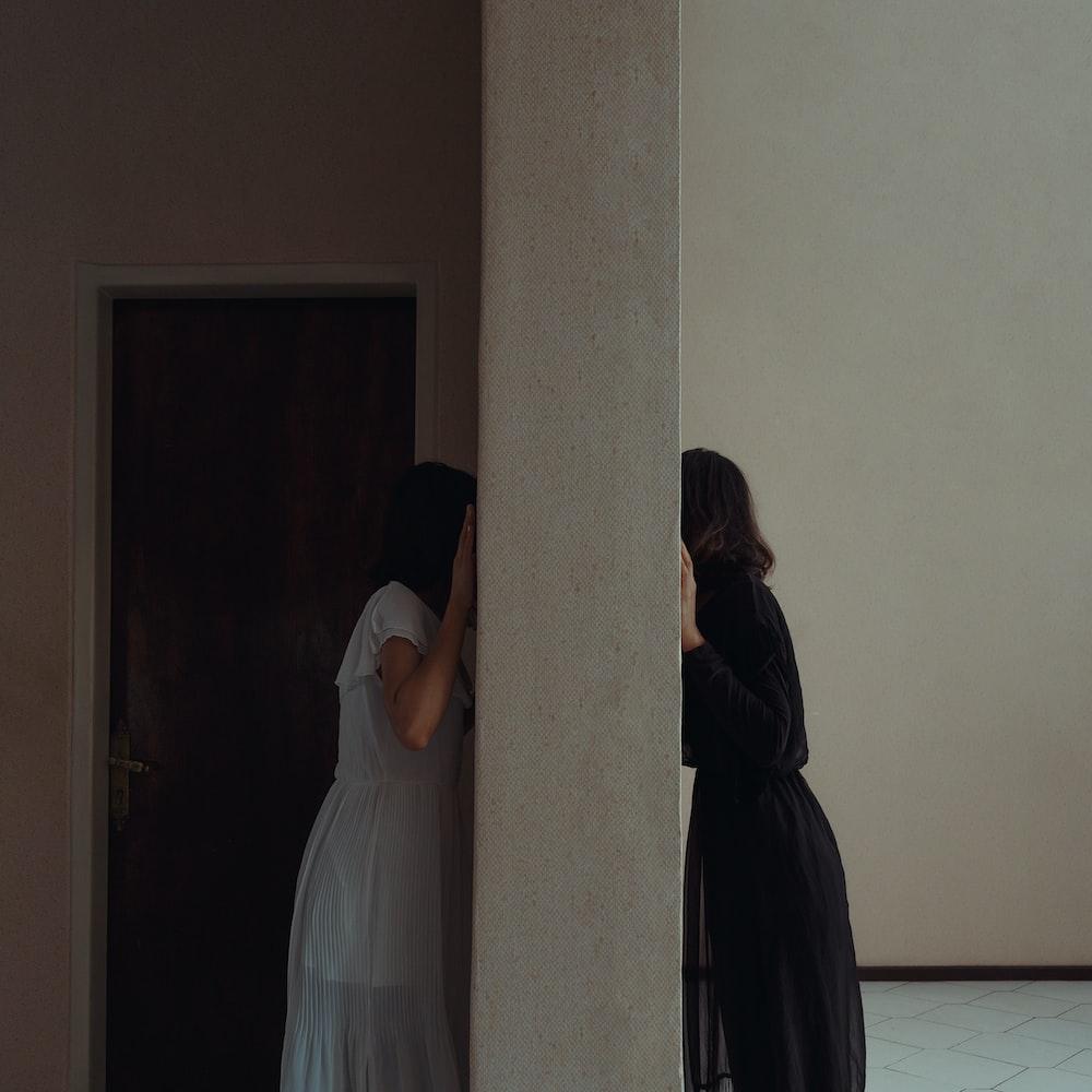 woman in white dress standing beside woman in black hijab