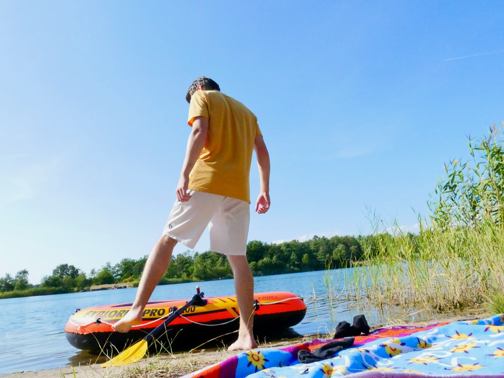 man in yellow polo shirt and white shorts standing on red and blue kayak during daytime