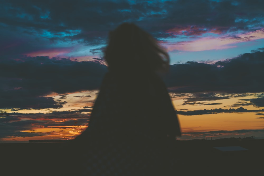 silhouette of woman sitting on beach during sunset