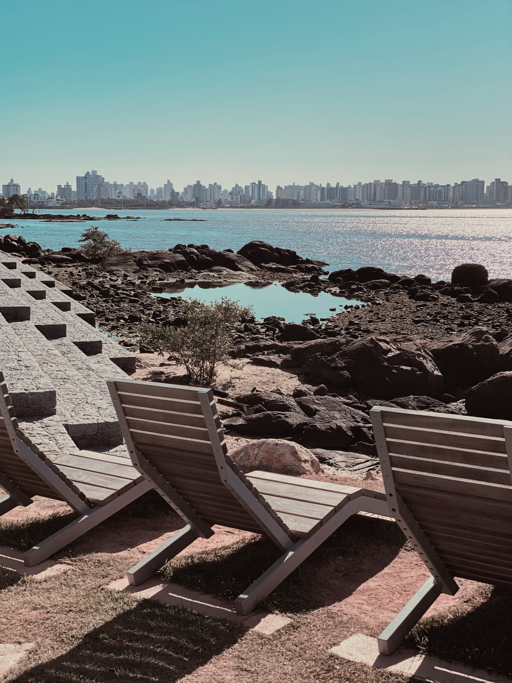 brown wooden bench on gray rocky shore during daytime