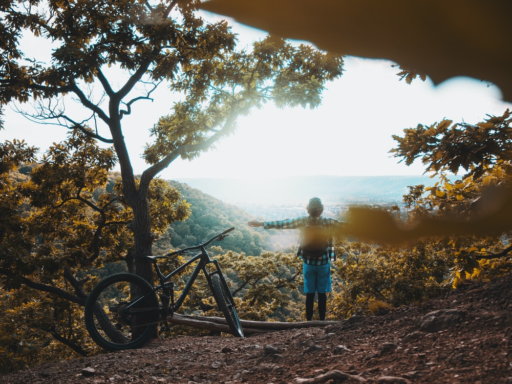 man in blue shirt standing beside black mountain bike near tree during daytime