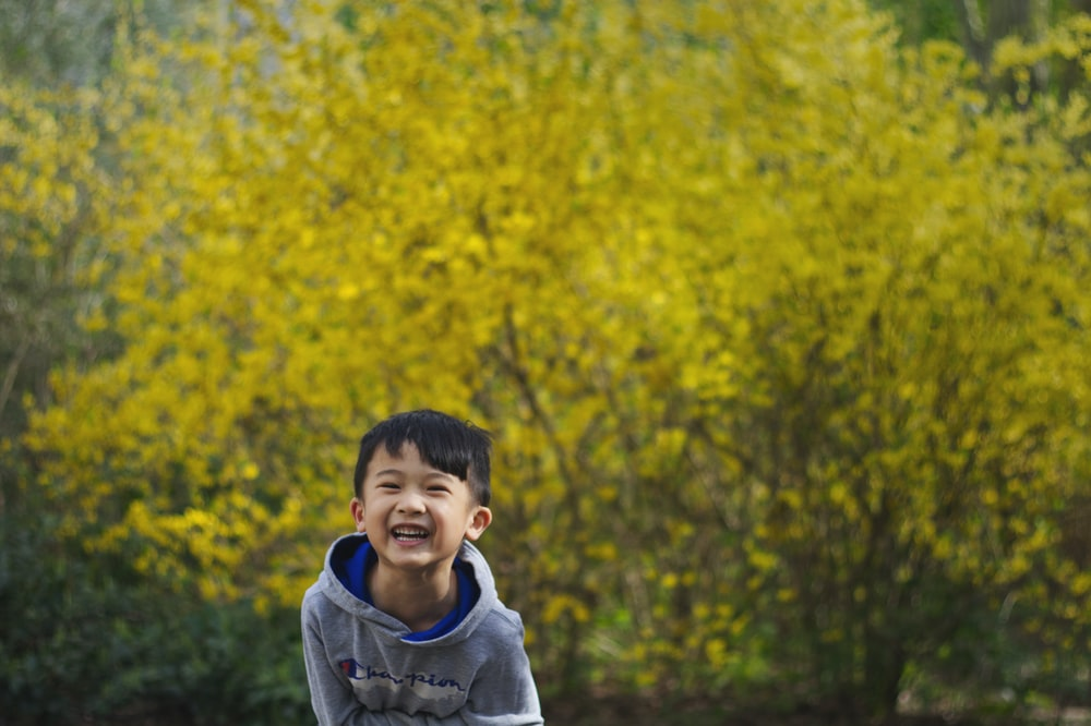 boy in gray hoodie standing near yellow leaf trees during daytime