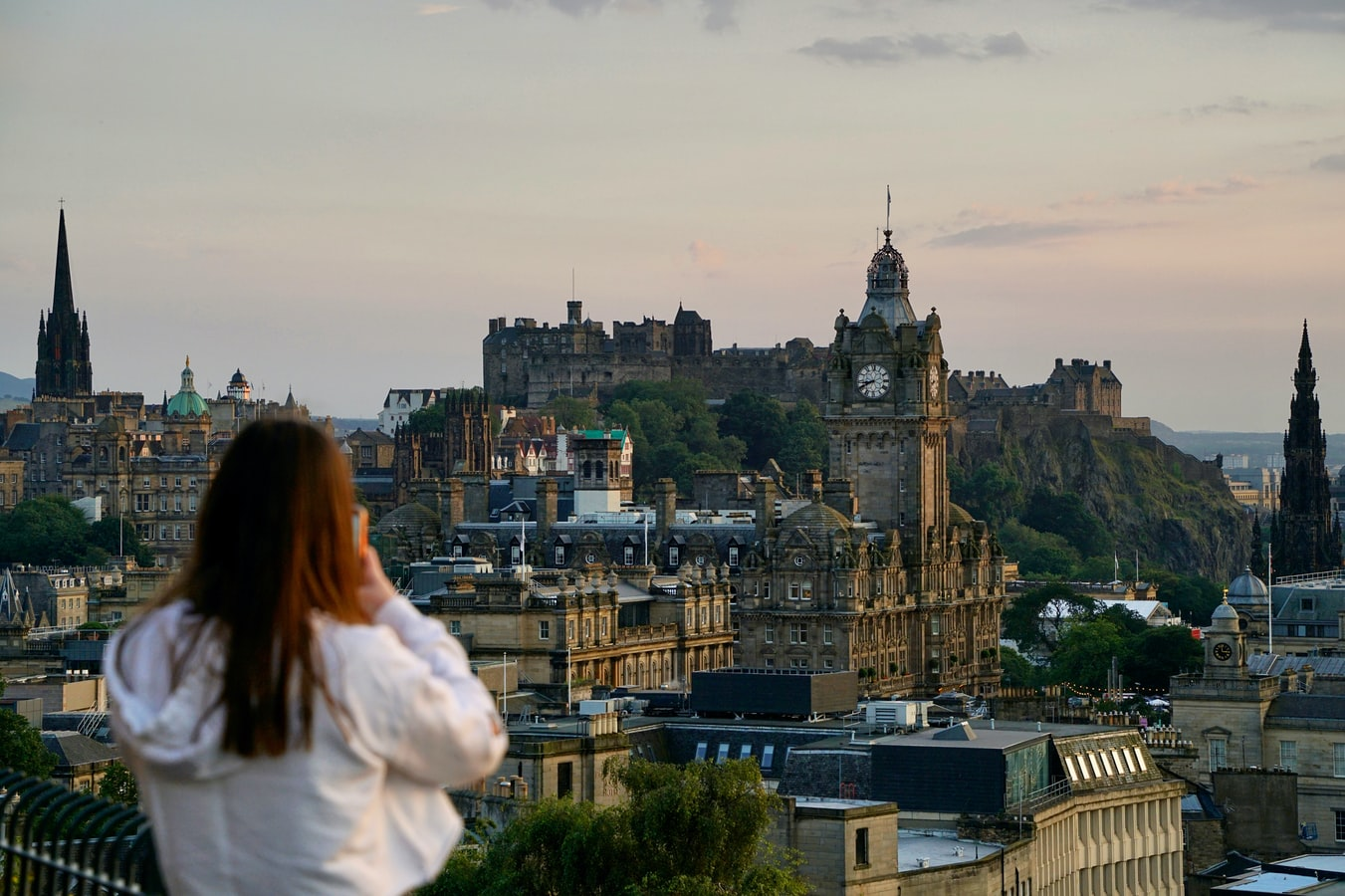 A girl taking a photo of the Edinburgh skyline