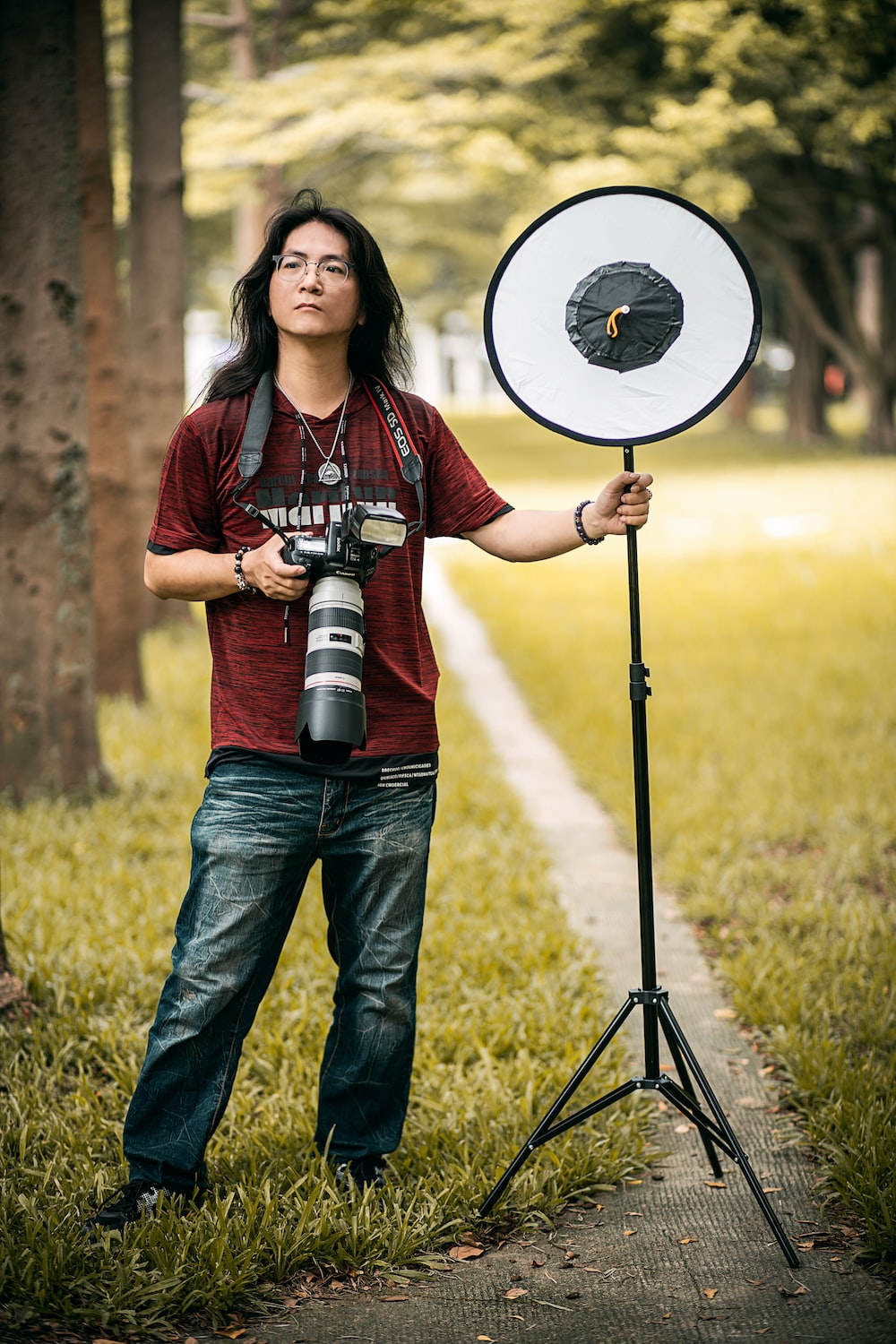 woman in red and white plaid shirt and blue denim jeans holding black and white camera