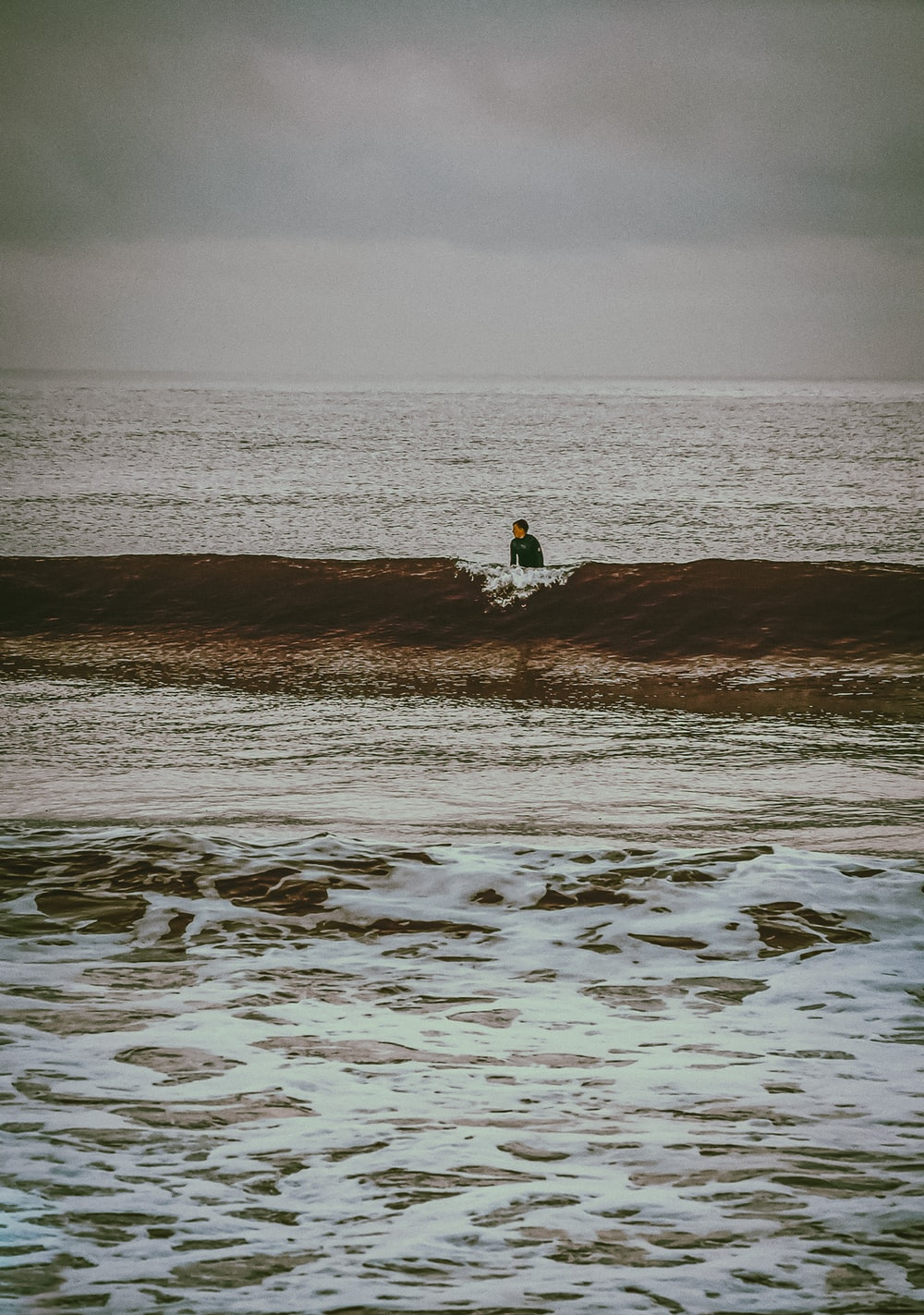 person in white shirt sitting on brown sand near body of water during daytime