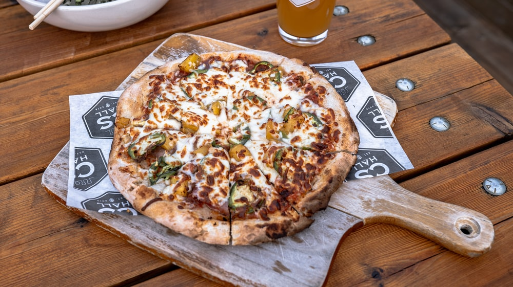 pizza on brown wooden board