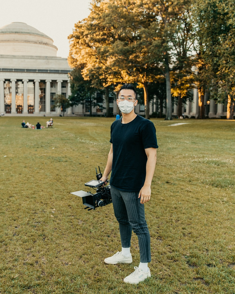 man in black crew neck t-shirt and blue denim jeans standing on green grass field
