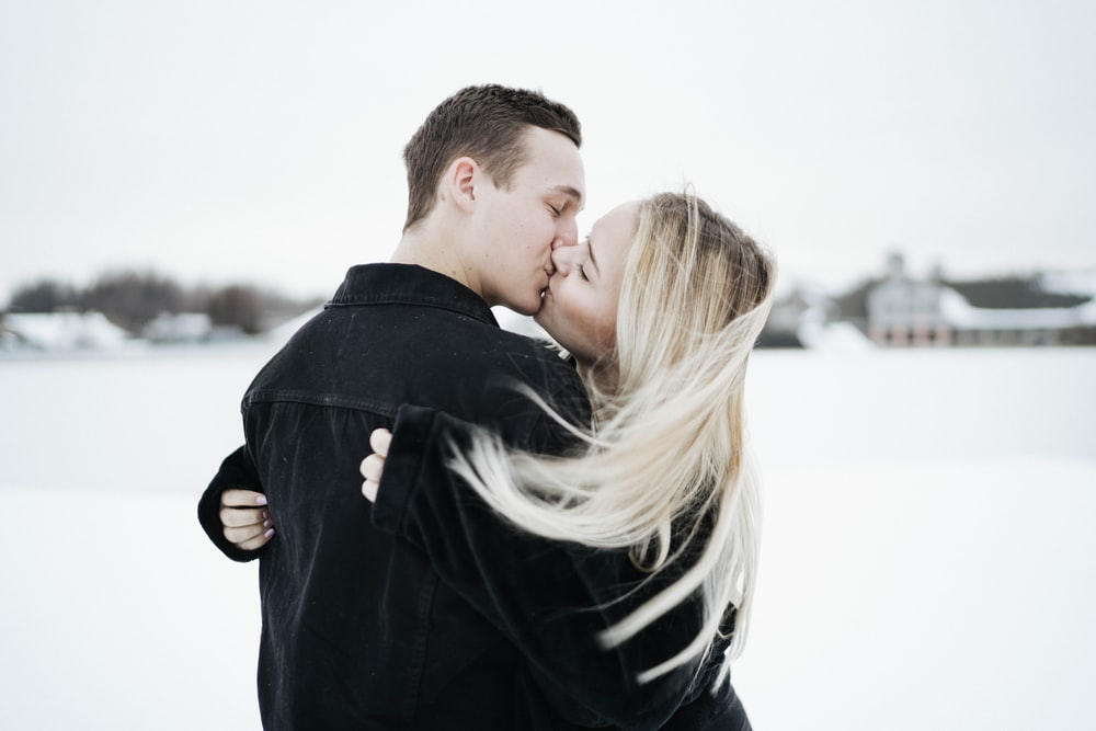 man in black coat kissing woman in black and white shirt