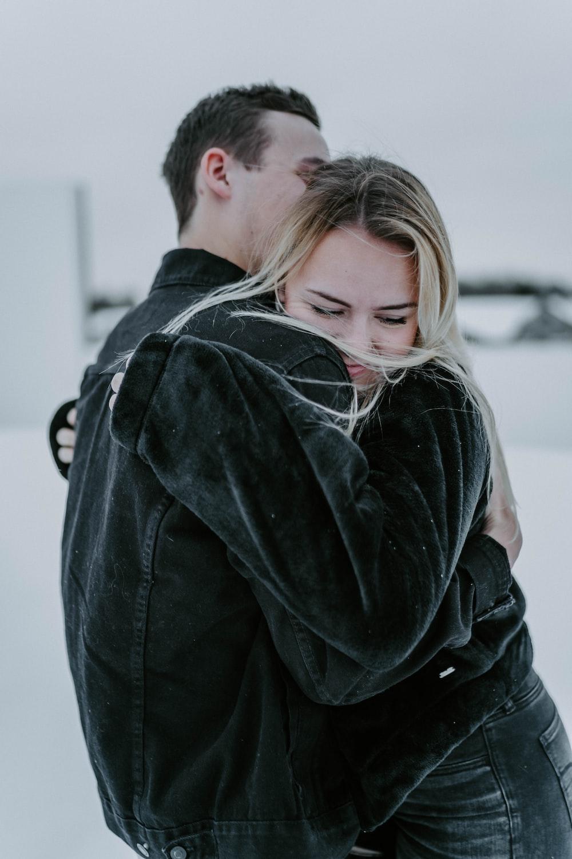 man in black jacket hugging woman in black coat